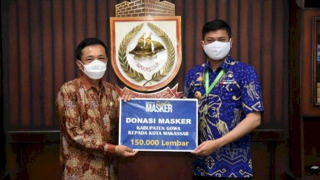Bupati Kabupaten Gowa, Adnan Purichta Ichsan menyerahkan bantuan 150 ribu masker secara simbolis kepada Pj Wali Kota Makassar, Prof Rudy Djamaluddin, Jumat (10/7/2020). (ist)