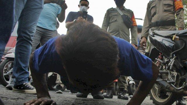 Satpol PP Makassar menghukum Pus-up warga yang melintas di perbatasan tanpa menggunakan masker, Minggu (12/7/2020). (ist)