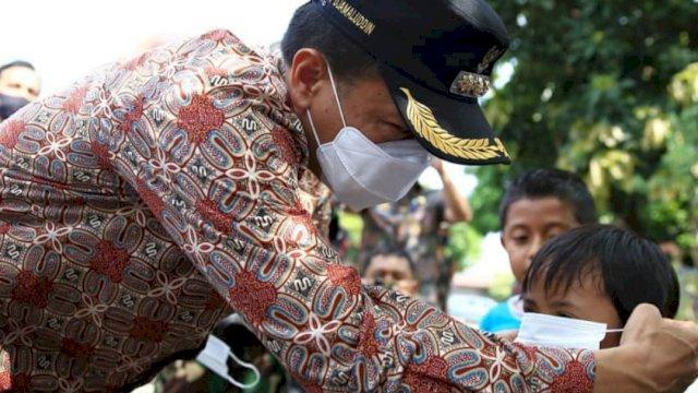 Pj Wali Kota Makassar, Prof Rudy Djamaluddin memakaikan masker ke salah satu anak yang tengah bermain, belum lama ini. (Ist)