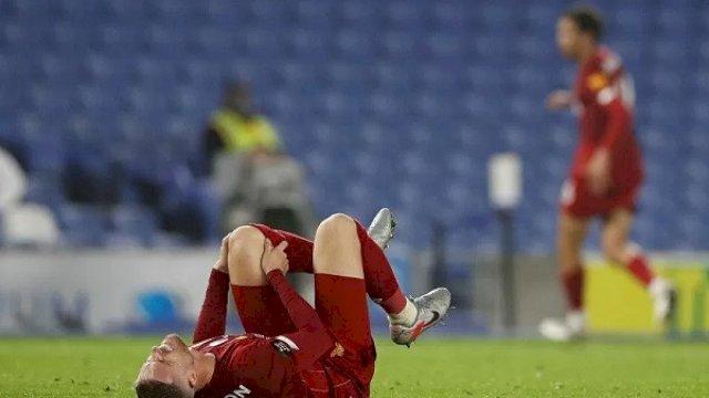 Kapten Liverpool Jordan Henderson tampak meringis kesakitan memegangi lutut kirinya ketika cedera di tengah laga lanjutan Liga Inggris melawan Brighton & Hove Albion yang digelar tanpa penonton karena pandemi COVID-19 di Stadion Amex, Brighton, Inggris, Rabu (8/7/2020). (ANTARA/REUTERS/POOL/Paul Childs)