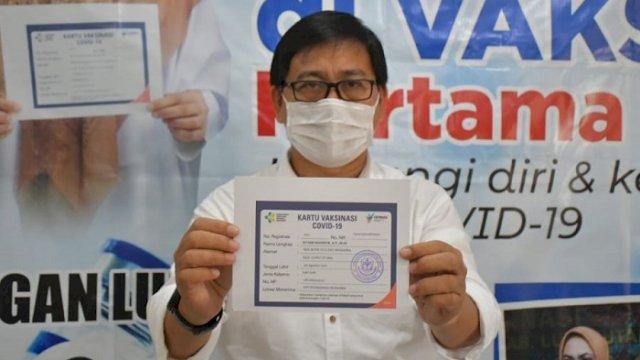 Wakil Bupati Luwu Utara, Suaib Mansur menunjukkan kartu usai menerima suntikan vaksim. ()