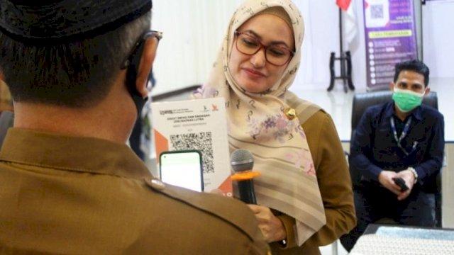 Bupati Luwu Utara, Indah Putri Indriani memegang barcode QRIS untuk pembayaran.