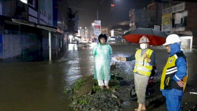 Wakil Bupati Luwu Utara, Suaib Mansur mengenakan payung saat meninjau titik genangan air di Kota Masamba, dini hari tadi.