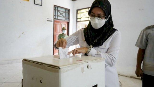 Bupati Luwu Utara, Indah Putri Indriani memasukkan kertas suara saat memberikan hak pilih di TPS 03 Desa Saptamarga.