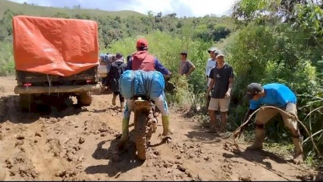 Sebuah angkutan barang dan kendaraan roda dua sedang melewati jalan yang rusak menuju Seko (5/8).
