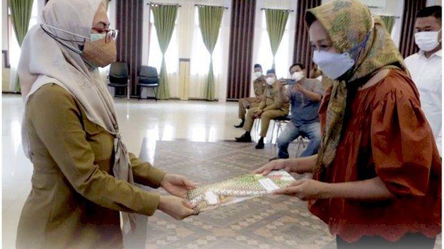 Bupati Luwu Utara, Indah Putri Indriani, saat menyerahkan SPPBJ kepada perusahaan pengembang pembangunan huntap.
