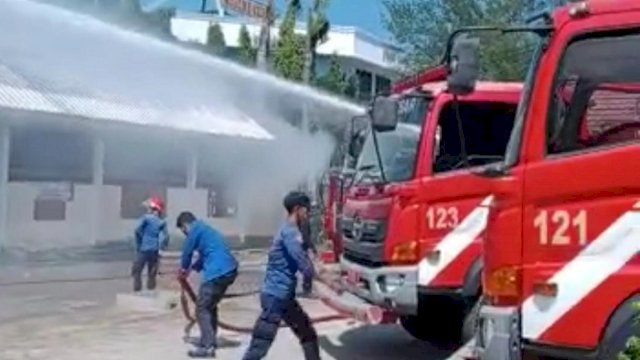 Petugas Dinas Pemadam Kebakaran Kota Makassar sedang berjibaku memadamkan api saat kebakaran di RSKD Dadi Makassar pada Minggu pagi (26/9/2021).