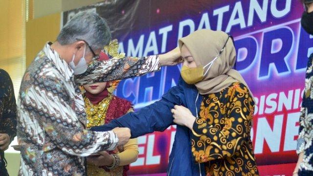 Ketua Pembina Yayasan Pendidikan Nobel Indonesia Badaruddin saat memasangkan almamater ke mahasiswa baru.